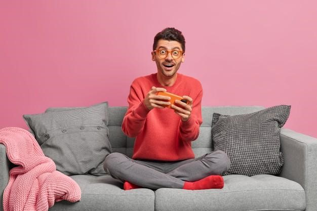 Человек играет в игру на телефоне